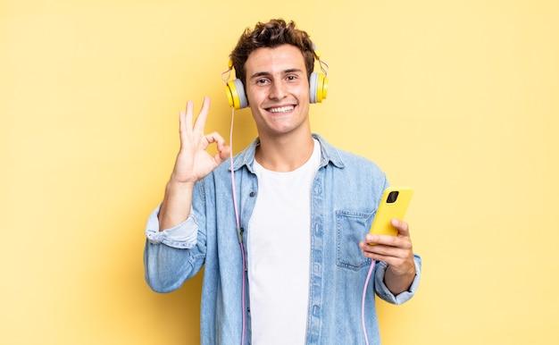 Czuję się szczęśliwy, zrelaksowany i usatysfakcjonowany, okazując aprobatę dobrym gestem, uśmiechając się. koncepcja słuchawek i smartfona