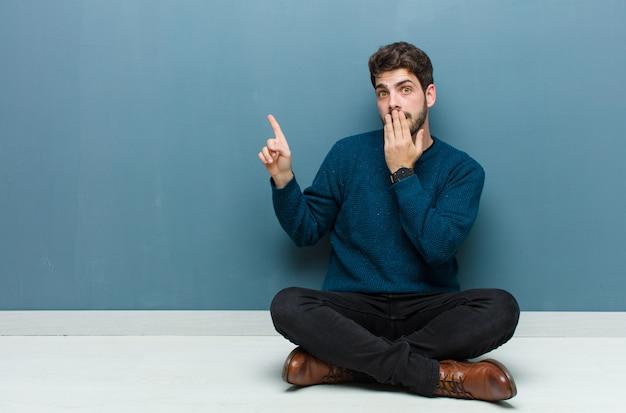 Czuje się szczęśliwy, zszokowany i zaskoczony, zasłaniając usta dłonią i wskazując na boczną przestrzeń kopii