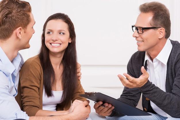 Czuję się teraz szczęśliwy. szczęśliwa młoda para patrząc na siebie, podczas gdy psychiatra ze schowkiem gestykuluje i uśmiecha się