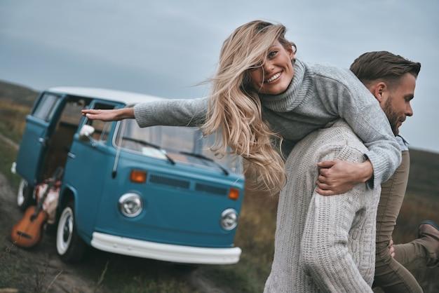 Czuję się wolny, by zrobić wszystko. przystojny młody mężczyzna niosący swoją atrakcyjną dziewczynę na ramionach i uśmiechnięty stojąc w pobliżu niebieskiego mini vana w stylu retro retro