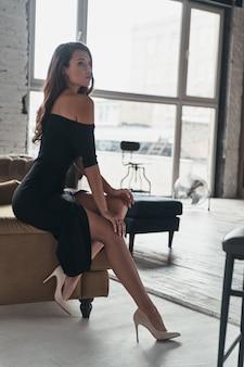 Czuję się wolny i zrelaksowany. atrakcyjna młoda kobieta w eleganckiej czarnej sukience z głębokim rozcięciem pozuje siedząc na kanapie