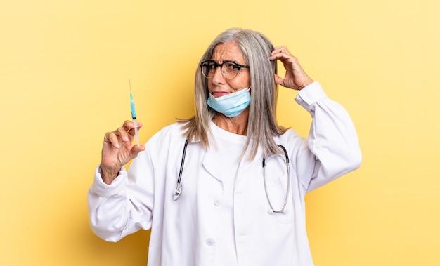 Czuję się zakłopotany i zdezorientowany, drapiąc się po głowie i patrząc w bok. koncepcja lekarza i szczepionki