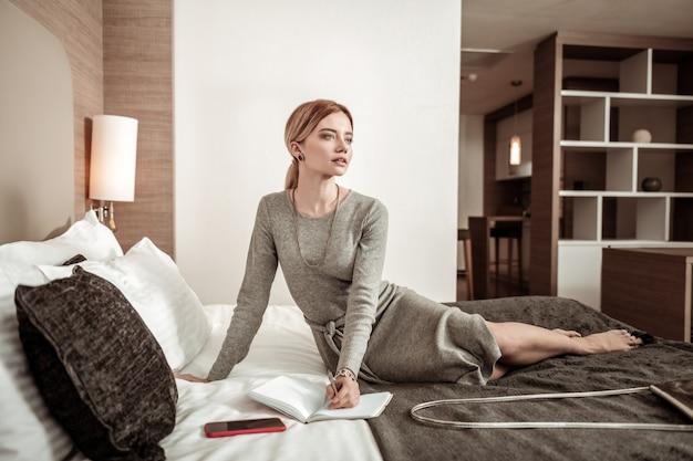 Czuję się zamyślony. zajęta kobieta sukcesu czuje się przemyślana, planując swój dzień podczas podróży służbowej