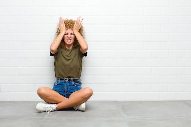 Czuje się zestresowany i niespokojny, przygnębiony i sfrustrowany bólem głowy, podnosząc obie ręce do głowy