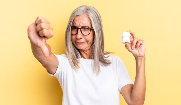 Czuję się zły, zły, zirytowany, rozczarowany lub niezadowolony, pokazując kciuk w dół z poważnym spojrzeniem i trzymając butelkę tabletek