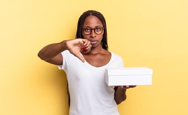 Czuję się zły, zły, zirytowany, rozczarowany lub niezadowolony, pokazując kciuk w dół z poważnym spojrzeniem i trzymając puste pudełko