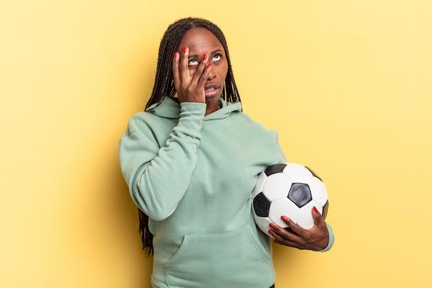 Czuję się znudzony, sfrustrowany i senny po męczącym, nudnym i żmudnym zadaniu, trzymając twarz dłonią. koncepcja piłki nożnej