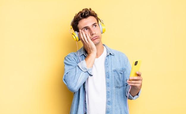 Czuję się znudzony, sfrustrowany i senny po męczącym, nudnym i żmudnym zadaniu, trzymając twarz dłonią. koncepcja słuchawek i smartfona