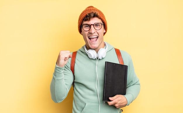 Czuję się zszokowany, podekscytowany i szczęśliwy, śmiejąc się i świętując sukces, mówiąc wow!. koncepcja studenta