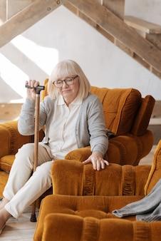 Czuję twoją obecność. miła, smutna, nieszczęśliwa kobieta siedząca w pobliżu pustego fotela i trzymająca laskę z nostalgią za swoją przeszłością
