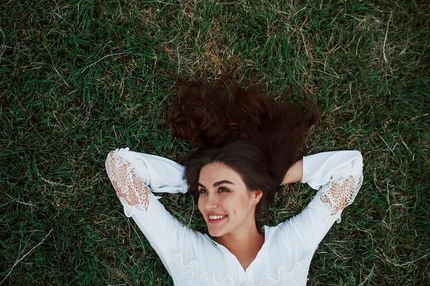 Czuje wolność. dziewczyna leżąc na zielonej trawie i odpocząć.