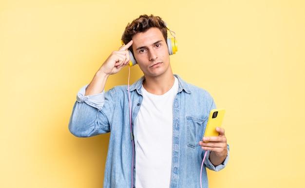 Czujesz się zdezorientowany i zdezorientowany, pokazując, że jesteś szalony, szalony lub oszalały. koncepcja słuchawek i smartfona