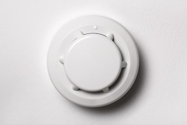 Czujnik dymu na białym suficie. bądź bezpieczny w domu. kontrola domu i bezpieczeństwo
