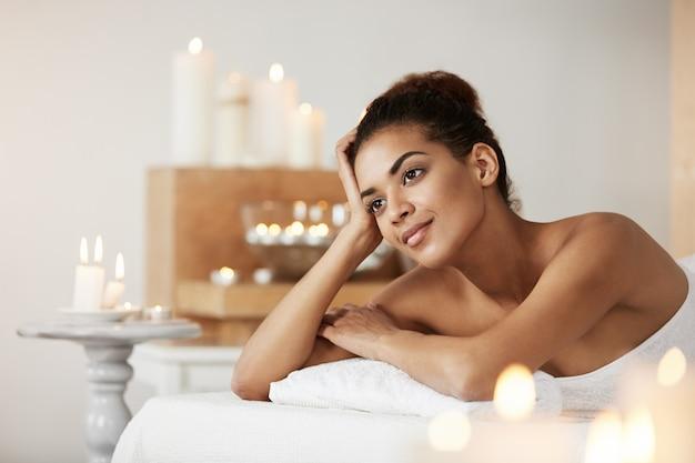 Czuła afrykańska kobieta uśmiecha się patrzeć w odległość relaksuje w zdroju salonie.