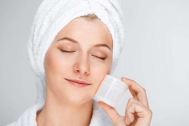 Czuła blond kobieta z kąpielowym ręcznikiem na włosy pokazuje śmietankę