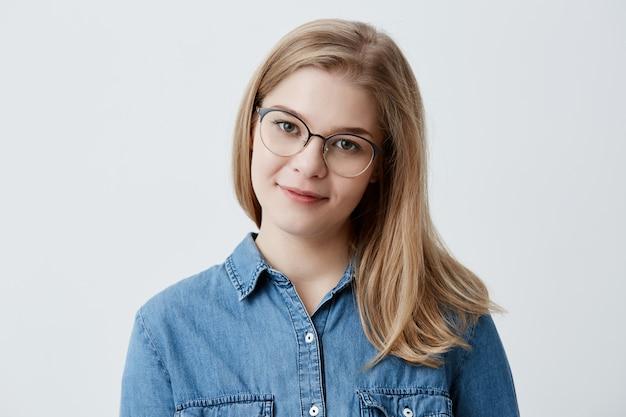 Czuła blondynka nastolatka o zdrowej skórze, ubrana w dżinsową koszulę i okulary, z wyrazem zadowolenia lub zamyślenia. kaukaski młoda kobieta model z blond włosy pozowanie w pomieszczeniu
