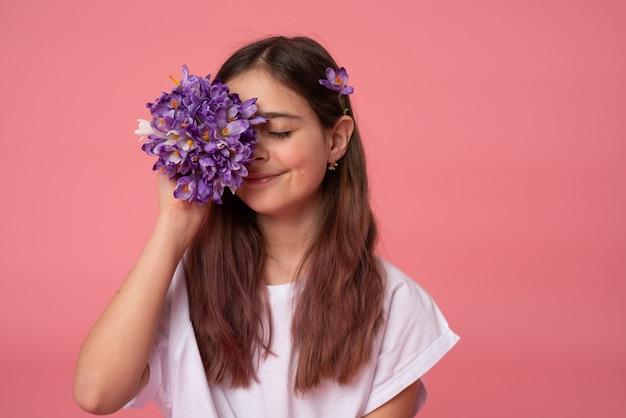 Czuła brunetki dziewczyna w białym koszulki coned-one oku z purpurowymi wiosennymi kwiatami odizolowywającymi