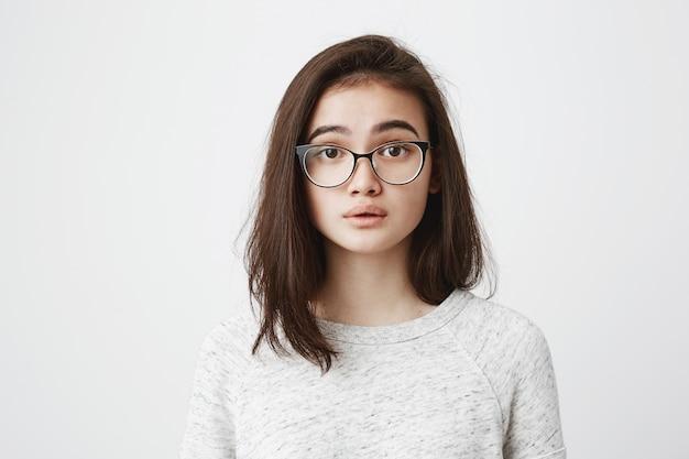 Czuła brunetki kobieta w okularach ma spokojny lub zadowolony wyraz