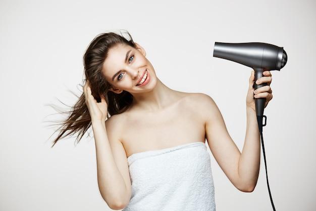 Czuła brunetki piękna kobieta ono uśmiecha się nad białym bakground w ręcznikowym suszarniczym włosy. beauty spa i kosmetologia.
