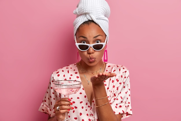 Czuła ciemnoskóra kobieta przesyła buziaka, ma zaokrąglone usta, trzyma koktajl, nosi modne okulary przeciwsłoneczne, ręcznik na głowie