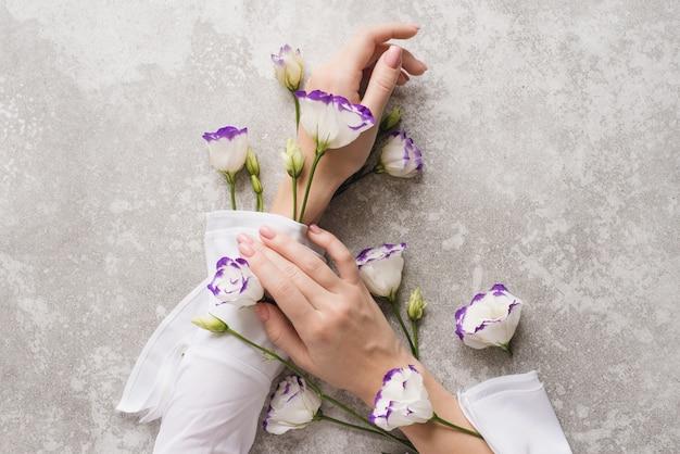 Czuła dłoń kobiety z nagim manicure i kwiatami eustoma.