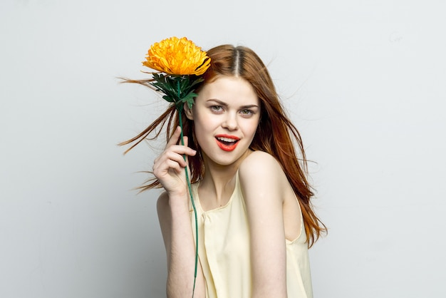 Czuła dziewczyna z żółtym kwiatem w jej rękach