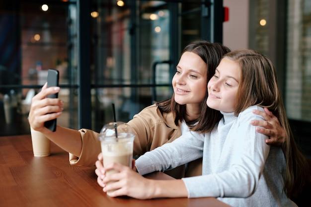 Czuła matka i córka z napojami, patrząc na aparat smartfona podczas robienia selfie w kawiarni