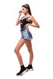 Czuła młoda brunetka modelka patrzy na prawo ubrana w krótkie niebieskie dżinsy