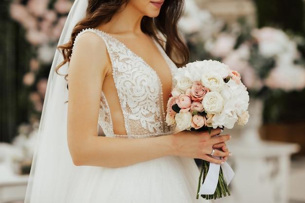 Czuła panna młoda trzyma w rękach bukiet z białych i różowych róż.
