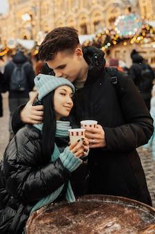 Czuła para trzyma na zewnątrz ciepłe napoje, kawę lub herbatę.