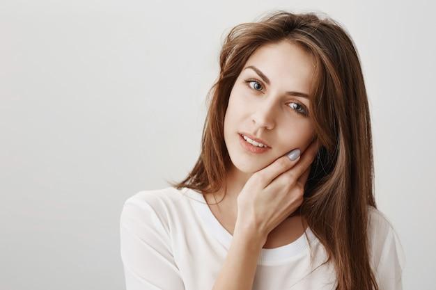 Czuła piękna kobieta dotyka miękkiej skóry i patrzy