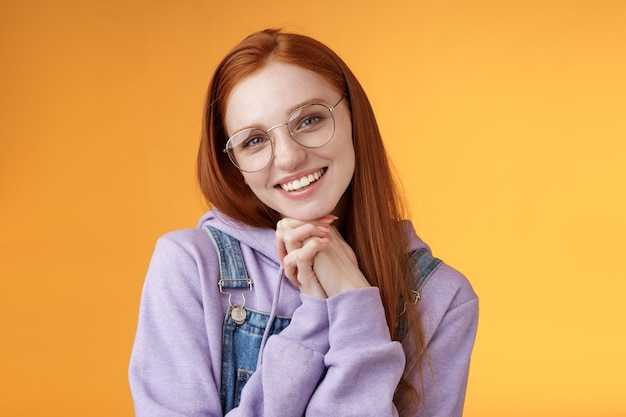 Czuła romantyczna urocza rudowłosa dziewczyna pochylona dłońmi z pochyloną głową słodka zalotna chichocząca uśmiechnięta kamera białe zęby w okularach z kapturem i kombinezonem w pobliżu pomarańczowego tła, zmysłowo się śmiejąc.