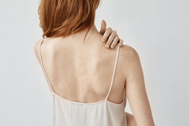 Czuła rudowłosa kobieta w bieliźnie stojąca z powrotem za pomocą osłony przeciwsłonecznej, niedobór melaniny