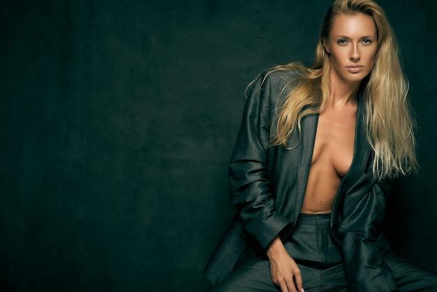 Czuła seksowna kobieta w męskim garniturze na nagim ciele z długimi blond włosami na ciemnym tle w studio