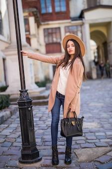 Czuła uśmiechnięta dama chodzi po ulicy i pozuje w swobodnym nowoczesnym płaszczu i kapeluszu
