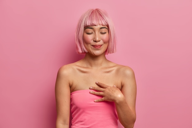 Czuła wzruszona kobieta zamyka oczy, trzyma rękę blisko serca, szczęśliwa z otrzymania prezentu, wspomina uroczą randkę, ufarbowała włosy na różowo, ubrana swobodnie,