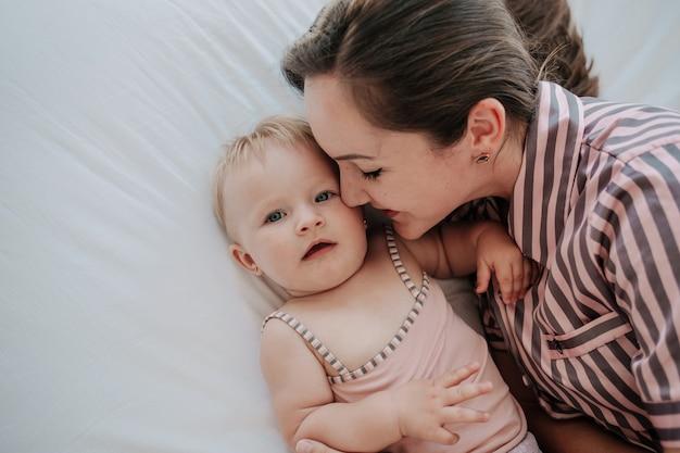 Czułe brunetki i córeczka na białej pościeli