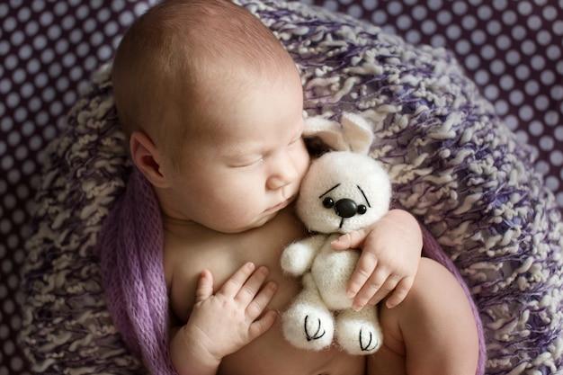 Czułe dziecko śpiące w koszu z dzianinową zabawką