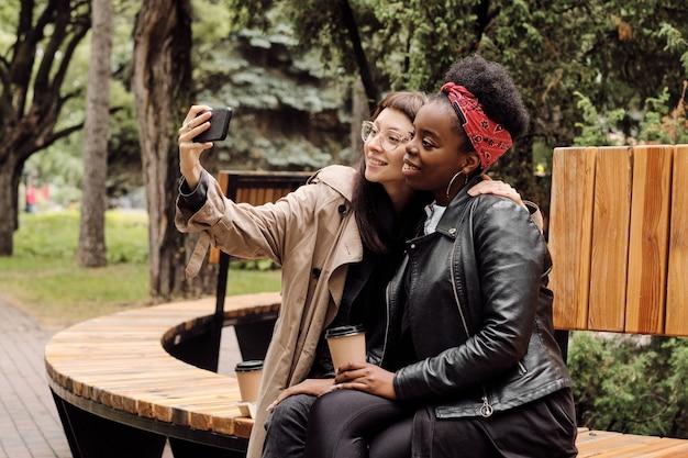 Czule dziewczyny robiące selfie w parku