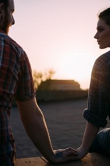 Czułe połączenie miłości. pierwsza randka. młoda para w centrum uwagi na pierwszym planie trzymając się za ręce, jasnym tle zachodu słońca. delikatny dotyk, hipsterska relacja, romantyczna koncepcja nastroju