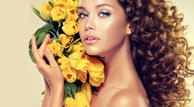 Czułe spojrzenie pięknych oczu młoda brązowowłosa kobieta z bukietem żółtych tulipanów
