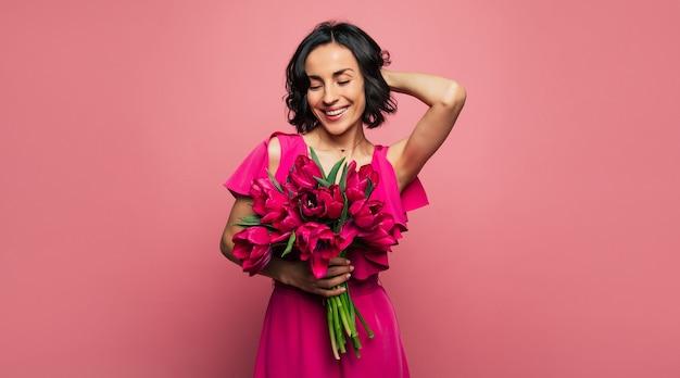 Czułość. dobrze ubrana kobieta trzyma w prawej dłoni bukiet tulipanów i pozuje z lewą ręką nad głową, uśmiechając się radośnie i patrząc w dół.