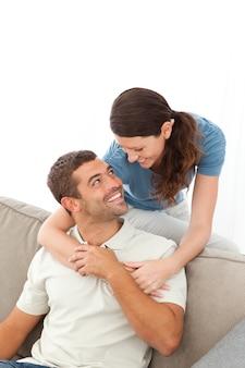Czuły kobieta przytulanie jej mąż relaksujący na kanapie