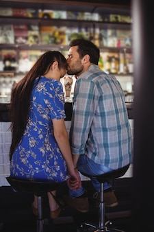 Czuły mężczyzna trzymając się za ręce podczas całowania kobiety przy ladzie