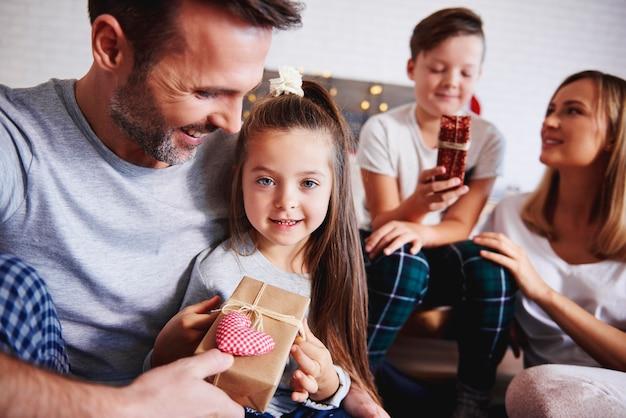 Czuły ojciec daje córce prezent pod choinkę