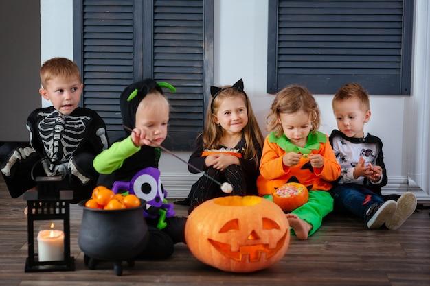 Czwórka dzieciaków w karnawałowych kostiumach świętuje halloween i bawi się dyniami i cukierkami