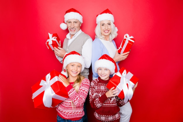 Czwórka krewnych - podekscytowane rodzeństwo i starsza para małżeńska dziadka i babci z prezentami, w dzianinowych uroczych tradycyjnych strojach x mas, odizolowani na czerwonej przestrzeni, cieszą się, promiennymi uśmiechami