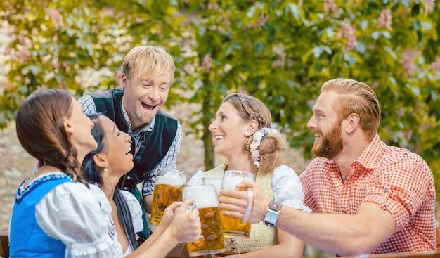Czwórka przyjaciół pije jednocześnie piwo w bawarskim ogródku piwnym
