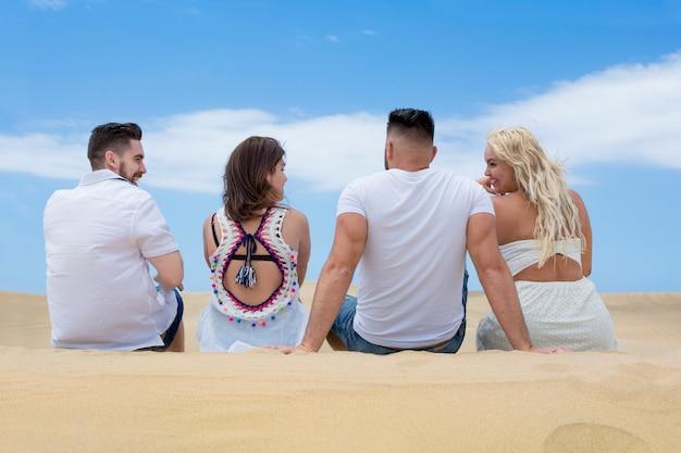 Czwórka przyjaciół siedzi plecami na blond piasku plaży, śmiejąc się i dobrze się bawiąc.