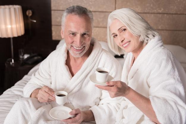 Czy chcesz kawę. wesoła uśmiechnięta para w wieku leżąc na łóżku i pijąc kawę, wyrażając radość